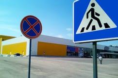 Två vägmärken på en bakgrund av en köpcentrum och en blå himmel royaltyfri bild