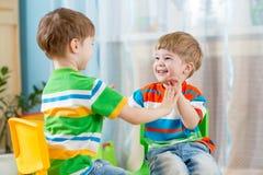 Två vänbarnpojkar spelar tillsammans inomhus royaltyfria foton