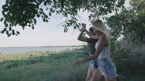 Två vänkvinnor som kör längs vägen på resanden Blondin och brunett som ler och har gyckel på semester steadicam stock video