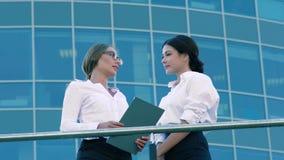Två vänliga kvinnliga coworkers som utomhus gör affär lager videofilmer