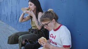 Två vänner äter ostburgare på gatan arkivfilmer