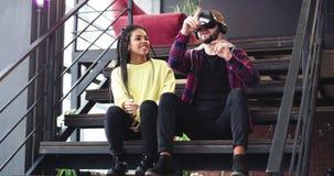 Två vänner en grabb och en afrikansk dam, undersökande mycket nyfiket exponeringsglas för en virtuell verklighet som ner sitter p lager videofilmer