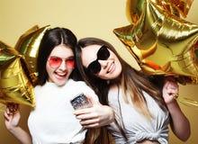 Två vänner för tonårs- flickor med guld- ballonger gör selfie på ett p Fotografering för Bildbyråer