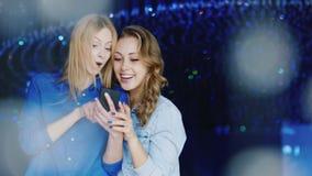 Två vänner för unga kvinnor använder telefonen på en nattklubb, positiva sinnesrörelser arkivfilmer