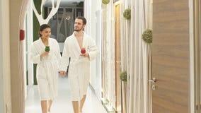 Två vänner går ner korridoren för behandlingar på Spa Sund livsstil arkivfilmer