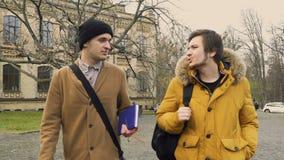 Två vänner går till universitetsområdet arkivfilmer