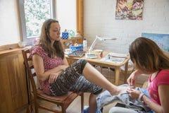 Två vänner gör en pedikyr pedikyrprocess och closeup för brunnsorttillvägagångssättmakro Hon applicerar fuktighetsbevarande hudkr Arkivfoto