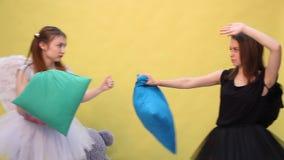 Två vänner har roliga slåss kuddar i form av en ängel och en demon lager videofilmer
