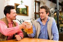 Två vänner i bayersk pub Arkivfoto