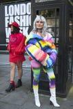 Två vänner i färgrik kläder som poserar nära ett svart telefonbås under London, danar vecka utvändiga Eudon Choi Royaltyfri Foto