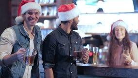 Två vänner i jultomtenhattar och flickan bak stock video