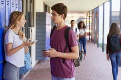 Två vänner med smartphones som talar i skolakorridor Arkivbild
