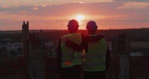 Två vänner och partners på konstruktionsplatsen på taket av byggnad som rymmer sig och ser fantastisk himmelsikt lager videofilmer