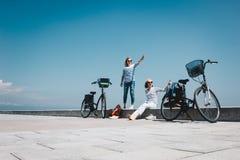 Två vänner på stranden med cyklar Royaltyfri Bild