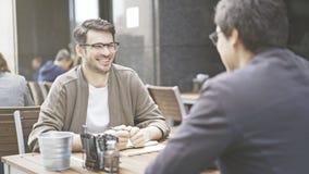 Två vänner skrattar på tabellen av kafét utomhus royaltyfria bilder