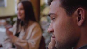 Två vänner som äter i det moderna kafét som sitter nära fönstret Ledsen grabbnärbild för framsida lager videofilmer