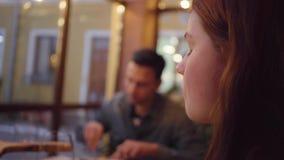 Två vänner som äter mat i det moderna kafét som sitter nära fönstret Den unga kvinnan med rött hår äter mål från djupt aluminium arkivfilmer