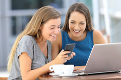 Två vänner som delar en smart telefon i en coffee shop arkivfoton