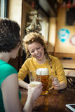 Två vänner som får toghether som dricker öl och laughin, inomhus Royaltyfria Bilder
