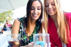 Två vänner som har gyckel med smartphones Fotografering för Bildbyråer