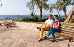 Två vänner som kopplar av på bänken efter en promenad Arkivfoto