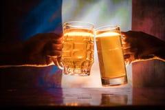 Två vänner som rostar (klirra) med exponeringsglas av ljust öl på baren Härlig bakgrund med suddig sikt av flaggan av Frankrike S fotografering för bildbyråer