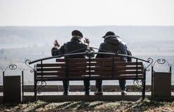 Två vänner som sitter på bänken Fotografering för Bildbyråer