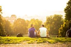 Två vänner som sitter på kullen, Prague, august 2015 Fotografering för Bildbyråer