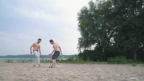 Två vänner som spelar fotboll på sanden nära flodkonkurrensen mellan folkvänner har en gyckel som spenderar tillsammans lager videofilmer