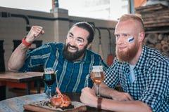 Två vänner som stöttar olika lag som sitter i bar fotografering för bildbyråer