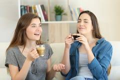 Två vänner som talar och tycker om en kaffekopp Fotografering för Bildbyråer