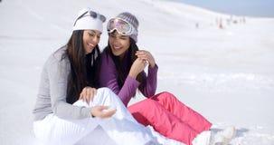 Två vänner som tillsammans sitter på Sunny Ski Hill arkivfoton