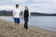 Två vänner som tillsammans talar och promenerar stranden arkivbild
