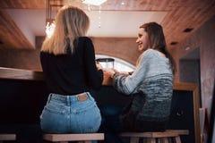Två vänner som tillsammans tycker om kaffe i en coffee shop, som de sitter på prata för tabell Fotografering för Bildbyråer