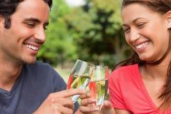 Två vänner som trycker på exponeringsglas av champagne Arkivbilder