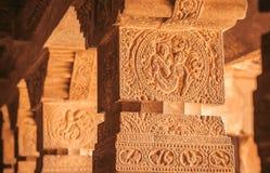 Två vänner tillsammans på kolonnlättnad av den hinduiska templet för 7th århundrade, stad Badami, Indien Sniden arkitektur av Asi Royaltyfri Foto