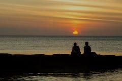 Två vänner vid havet som tycker om solnedgång Arkivfoton