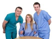 Två vårdare som lyfter upp en inaktiverad person Fotografering för Bildbyråer
