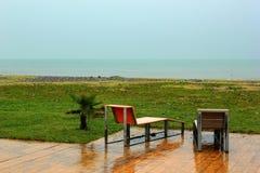 Två våta stolar på den tomma stranden på den regniga dagen i Batumi, Georgia Royaltyfria Bilder