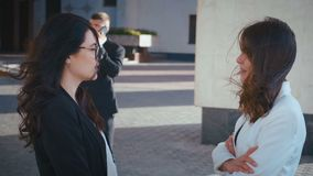 Två vackra affärskvinnor som talar med varandra De chattar och har kul tillsammans I bakgrundskontor stock video