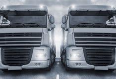 Två vanliga lastbilar på en cyan färg för huvudväg Royaltyfria Bilder
