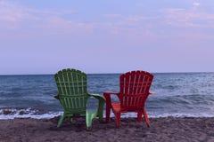 Två vardagsrumstolar på stranden Till hälften en vänd på en dagdrivare på stranden arkivfoto