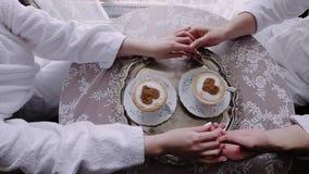 Två varje vänner som rymmer - annat händer satte deras händer på tabellen Det finns två koppar kaffe på tabellen lager videofilmer
