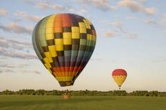 Två varmluftsballonger i ett fält Arkivbild