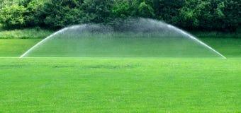 Två vattenspridare på gräsmatta Fotografering för Bildbyråer