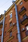 Två ventilerande rör för metallluft som körs längs fasaden av en tegelstenbyggnad arkivbild