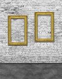 Två vertikala guld- ramar på tegelstenväggen arkivbild