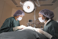 Två veterinär- kirurger i fungeringsrum Arkivfoton