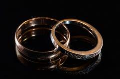 Två vigselringar av olika format som göras i guld på den svarta spegeln, ytbehandlar royaltyfri bild