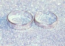 Två vigselringar av vit guld på silver blänker gnistrandet Arkivfoton